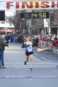 Jonathan Aziz of Boulder, CO breaks the tape first in the men's 5k at the 2017 Troy Turkey Trot in Troy, NY on Thanksgiving Day.